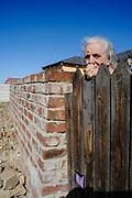 Oude vrouw kijkt toe op de wegwerkzaamheden rondom haar huis. (WK 2010, Zuid Afrika)