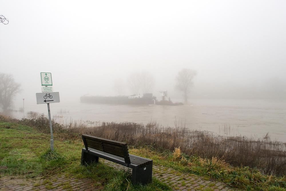 Bij Lathum vaart een schip over de IJssel, die buiten haar oevers treedt.<br /> <br /> A boat at the IJssel at high tide.