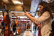 A woman examines a violin displayed by the Chamber of Commerce of Cremona. Cremona, home of Antonio Stradivarius, has long been a center for violin making.