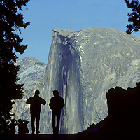 Tourists at Glacier Point in California's Yosemite National Park walk in front of Half Dome, its iconic monolith.