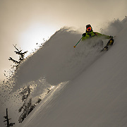 Tyler Hatcher makes huge powder turns in the Cascade Mountains of Washington at sunset.