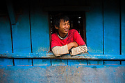 A young man looks out the window of a blue house in the village of Landruk along the Annapurna Sanctuary Trek, Himalaya Mountains, Nepal.