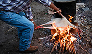 A man prepares a turkey's skin for slaughter, burning the feathers that remained after it was plucked. The meat was served to wedding guests in mole, a traditional Oaxacan dish.  Nick Wagner / Alexia Foundation