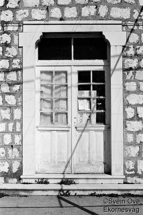 Kroatia 2012-06.<br /> Ei gammel, hvit dør på en bygning i hovedgaten på Lopud i Kroatia.<br /> Foto: Svein Ove Ekornesvåg