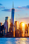 Freedom Tower, One WTC, rises above the New York skyline at sunset in Lower Manhattan Financial District, New York City.