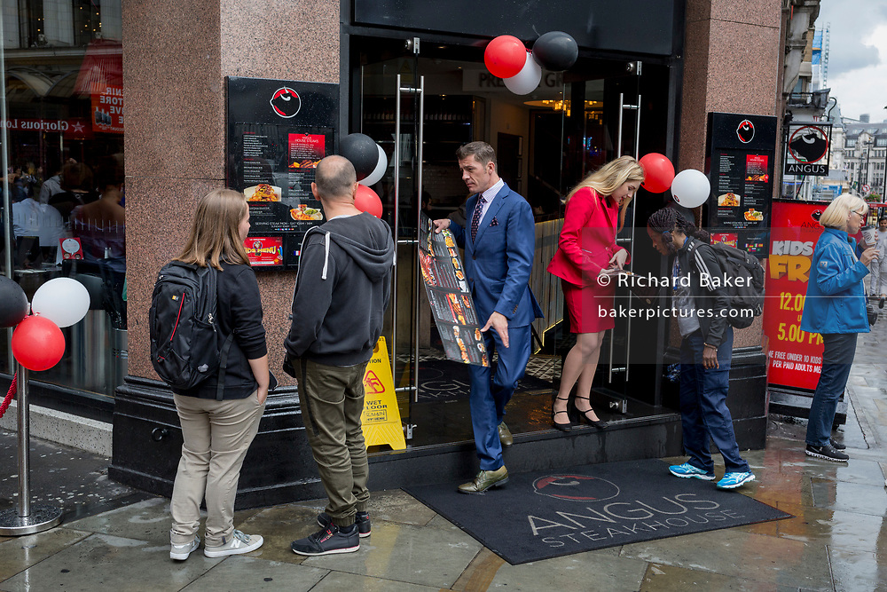 Staff with Angus Steakhouse show their menu to passers-by on Coventry Street, on 13th August 2018, in London, England. Angus Steakhouse is the original chain of steak restaurants based in central London's West End and has been serving both Londoners and visitors alike for 50 years.