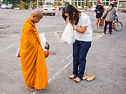 "14 FEBRUARY 2014 - BANGKOK, THAILAND:  A woman presents alms and prays with a novice monk on Makha Bucha Day at Wat That Thong (also called Wat Tad Tong) in Bangkok. The aims of Makha Bucha Day are: not to commit any kind of sins, do only good and purify one's mind. It is a public holiday in Cambodia, Laos, Myanmar and Thailand. Many people go to the temple to perform merit-making activities on Makha Bucha Day. The day marks four important events in Buddhism, which happened nine months after the Enlightenment of the Buddha in northern India; 1,250 disciples came to see the Buddha that evening without being summoned, all of them were Arhantas, Enlightened Ones, and all were ordained by the Buddha himself. The Buddha gave those Arhantas the principles of Buddhism, called ""The ovadhapatimokha"". Those principles are:  1) To cease from all evil, 2) To do what is good, 3) To cleanse one's mind. The Buddha delivered an important sermon on that day which laid down the principles of the Buddhist teachings. In Thailand, this teaching has been dubbed the ""Heart of Buddhism.""   PHOTO BY JACK KURTZ"