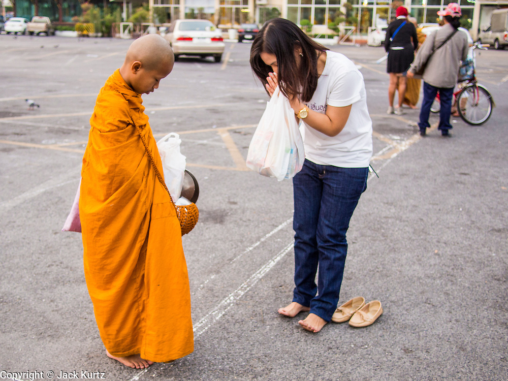"""14 FEBRUARY 2014 - BANGKOK, THAILAND:  A woman presents alms and prays with a novice monk on Makha Bucha Day at Wat That Thong (also called Wat Tad Tong) in Bangkok. The aims of Makha Bucha Day are: not to commit any kind of sins, do only good and purify one's mind. It is a public holiday in Cambodia, Laos, Myanmar and Thailand. Many people go to the temple to perform merit-making activities on Makha Bucha Day. The day marks four important events in Buddhism, which happened nine months after the Enlightenment of the Buddha in northern India; 1,250 disciples came to see the Buddha that evening without being summoned, all of them were Arhantas, Enlightened Ones, and all were ordained by the Buddha himself. The Buddha gave those Arhantas the principles of Buddhism, called """"The ovadhapatimokha"""". Those principles are:  1) To cease from all evil, 2) To do what is good, 3) To cleanse one's mind. The Buddha delivered an important sermon on that day which laid down the principles of the Buddhist teachings. In Thailand, this teaching has been dubbed the """"Heart of Buddhism.""""   PHOTO BY JACK KURTZ"""