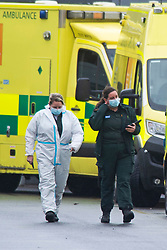© Licensed to London News Pictures 05/01/2021.        Dartford, UK. Paramedics wearing PPE looking exhausted as they walk back to their ambulance. A long line of ambulances outside Darent Valley Hospital in Dartford, Kent this afternoon. As the number of seriously ill Coronavirus patients continues to grow some patients are having to be transferred miles away from Kent to help with the critical care bed shortage. Photo credit:Grant Falvey/LNP