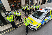Mounting police personnel wearing face masks stand by Animal Rebellion activists, who glued themselves inside a pink Truck and parked it in Victoria Street outside the department for social care on Thursday, Sept 3, 2020. Environmental non-violent activists group Extinction Rebellion enters its 3rd day of continuous ten days to disrupt political institutions throughout peaceful actions swarming central London into a standoff, demanding that central government obeys and delivers Climate Emergency bill.