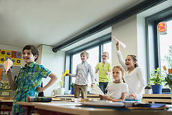 School children playing with paper airplanes in classroom, Munich, Bavaria, Germany