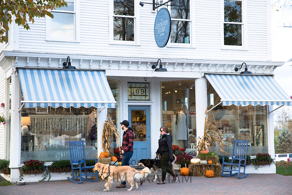 Local people walking dogs past The Country Store on Main Street in Stowe, Vermont, USA