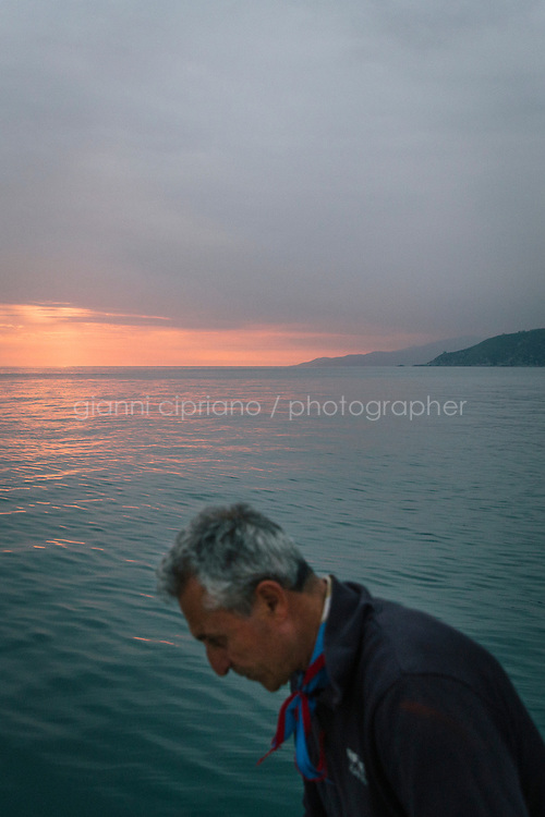 """PISCIOTTA, ITALY - 21 APRIL 2018: Fisherman Vittorio Rimbaldo (56) is seen here on his fishing boat as he gets ready to fish alici di Menaica (Menaica anchovies) in Pisciotta, Italy, on April 21st 2018.<br /> <br /> Former restaurant owners Donatella Marino and her husband Vittorio Rimbaldo have spent the recent years preparing and selling salted anchovies, called alici di menaica, to a growing market thanks to a boost in visibility from the non-profit Slow Food.  The ancient Menaica technique is named after the nets they use brought by the Greeks wherever they settled in the Mediterranean. Their process epitomizes the concept of slow food, and involves a nightly excursion with the special, loose nets that are built to catch only the larger swimmers. The fresh, red anchovies are immediately cleaned and brined seaside, then placed in terracotta pots in between layers of salt, to rest for three months before they're aged to perfection.While modern law requires them to use PVC containers for preserving, the government recently granted them permission to use up to 10 chestnut wood barrels for salting in the traditional manner. The barrels are """"washed"""" in the sea for 2-3 days before they're packed with anchovies and sea salt and set aside to cure for 90 days. The alici are then sold in round terracotta containers, evoking the traditional vessels that families once used to preserve their personal supply.<br /> <br /> Unlike conventional nets with holes of about one centimeter, the menaica, with holes of about one and half centimeters, lets smaller anchovies easily swim through. The point may be to concentrate on bigger specimens, but the net also prevents overfishing."""