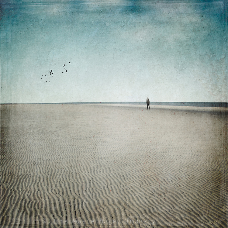 Man strolling along the seashore on an empty beach at low tide - photograph edited with texture overlays
