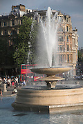 Fountain and passing red double decker bus, Trafalgar Square, London, England
