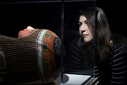 An exhibition at the National Museum of Scotland tells the story of one ancient Egyptian tomb across 1,000 years of use. Built around 1290 BC, the tomb was reused a number of times before being sealed in the 1st Century AD and left undisturbed until its excavation in the 19th Century<br /> <br /> Pictured: Dr Margaret Maitland, Senior Curator, Ancient Mediterranean at National Museums of Scotland with  Mummy-case of the priest Nehemsumut