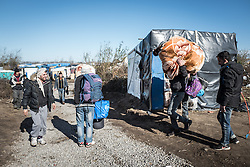 © London News Pictures. Calais, France. 04/03/16. Refugees gather together their posessions before leaving the Calais 'Jungle'. French authorities are clearing the southern half of the Calais 'Jungle' camp, which charities estimate to contain 3,500 people. Photo credit: Rob Pinney/LNP
