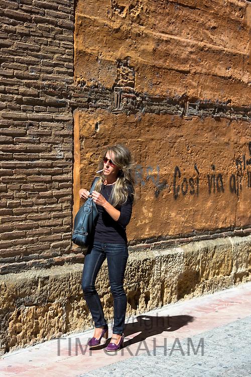 Spanish woman strolling in Calle Sacramento in Leon, Castilla y Leon, Spain