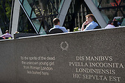 Modern English and ancient Latin marks the re-burial place of an unknown Roman girl near afternoon drinkers enjoying warm summer sunshine beneath the architecture of the Swiss Re building aka The Gherkin, on 17th Juy 2017, in the City of London, England.