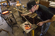 Blacksmith Fran Verga uses a metal working form to shape hot iron in an metal shop in Charleston, SC