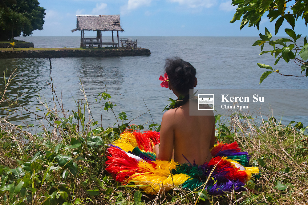 Yapese girl in grass skirt sitting by the ocean, Yap Island, Federated States of Micronesia