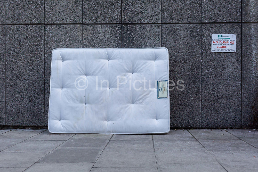 A stained white mattress leans against a wall next to a sign warning of £2,500 fines by the local authority for dumping or fly-tipping, on 6th February 2018, in the borough of Camden, London, England.