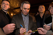 Yoshkar-Olinskii, Russia, 24/04/2005..Garry Kasparov signs autographs at a local residents' meeting in the Kazan area in central Russia as his bodyguards keep watch. Kasparov has been forced to travel with a team of bodyguards after recently being attacked and beaten with a chessboard by a man posing as a fan. .Kasparov, World Chess Champion for the last twenty years, recently retired from the professional game to devote his time to Russian politics, and is currently touring the country and founding a new political movement in opposition to President Valdimir Putin.