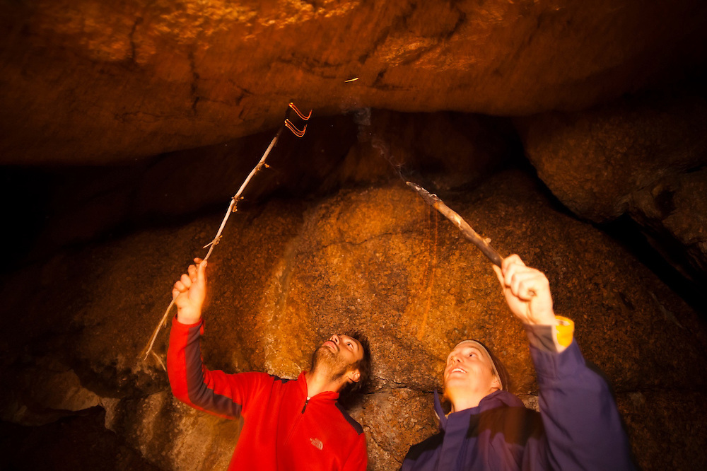 Marco Binotti (left) and David Coffey draw cave paintings with fire in their cave camp in McMurdy Park, Lost Creek Wilderness, Colorado.