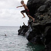 Honolulu, HI, July 17, 2007: A young boy jumps from a large crop of rock into the water at Waimea Bay on the North Shore of Oahu in Hawaii. (Photograph by Todd Bigelow/Aurora)