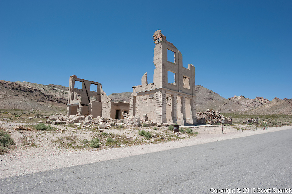 An old bank in a small desert town sits crumbling along the road.