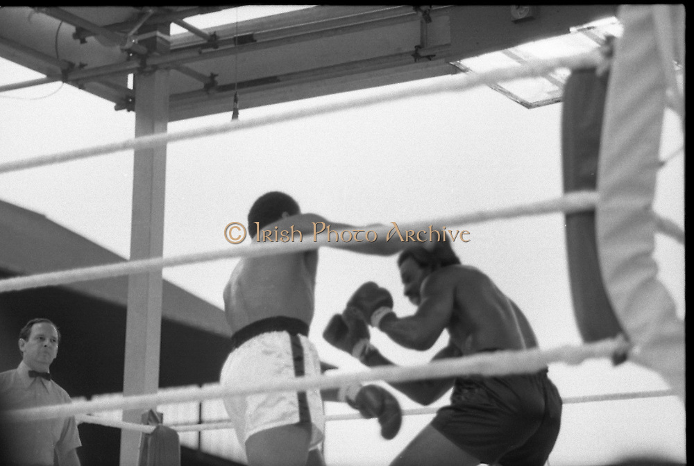 Ali vs Lewis Fight, Croke Park,Dublin.<br /> 1972.<br /> 19.07.1972.<br /> 07.19.1972.<br /> 19th July 1972.<br /> As part of his built up for a World Championship attempt against the current champion, 'Smokin' Joe Frazier,Muhammad Ali fought Al 'Blue' Lewis at Croke Park,Dublin,Ireland. Muhammad Ali won the fight with a TKO when the fight was stopped in the eleventh round.<br /> <br /> Image of Lewis as he ducks to avoid the swinging right of Ali.