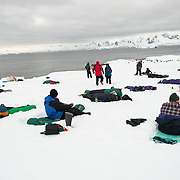 Tourists camp on the ice and snow at Hughes Bay on the Antarctic Peninsula. In the background, close to the water, a group of Gentoo penguins also rest on the ice.