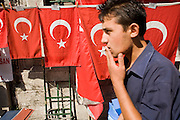 08 AUGUST 2007 -- ISTANBUL, TURKEY: A man walks past flags for sale in the Old Bazaar in Istanbul, Turkey. Istanbul, a city of about 14 million people, and the largest city in Turkey, straddles the Bosphorus Straits between Europe and Asia. It is one of the oldest cities in the world. It was once the center of the Eastern Roman Empire and was called Constantinople, named after the Roman Emperor Constantine. In 1453, Mehmet the Conqueror, Sultan of the Ottoman Empire, captured the city and made it the center of the Ottoman Turkish Empire until World War I. After the war, the Ottoman Empire was dissolved and modern Turkey created. The capitol was moved to Ankara but Istanbul (formerly Constantinople) has remained the largest, most diverse city in Turkey.    Photo by Jack Kurtz