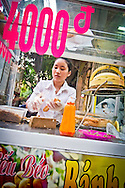 A girl serves Banh My Que on the street in Hanoi, Vietnam, Asia