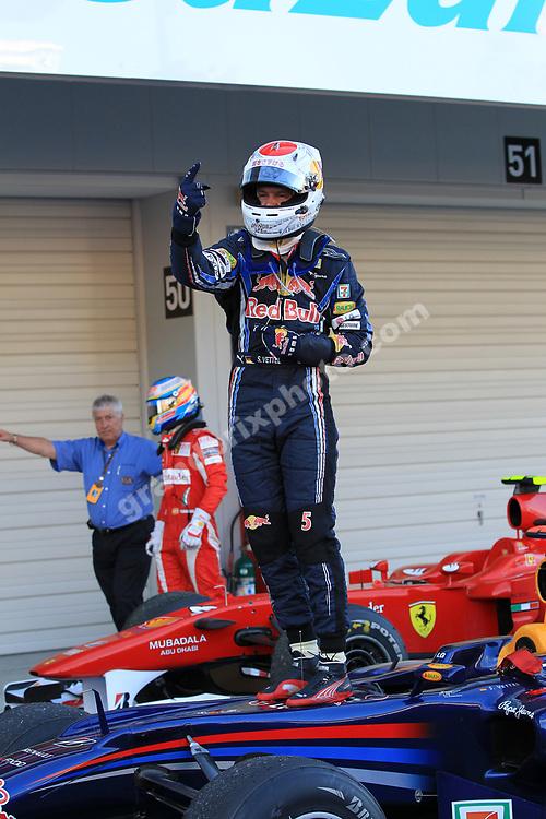 Sebastian Vettel (Red Bull-Renault) celebrates after the 2010 Japanese Grand Prix in Suzuka. In the background Fernando Alonso (Ferrari) and FIA official Herbie Blash. Photo: Grand Prix Photo
