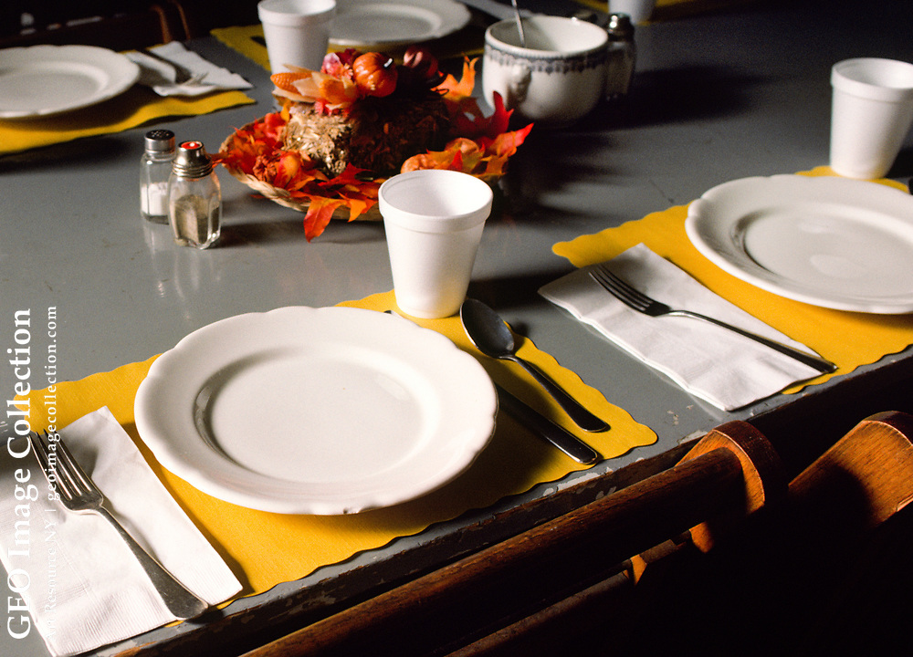 White ceramic plates and paper placemats are a modest New England table setting for a community supper meal in Strafford, Vermont. Styrofoam cups and cutlery share the simple gray tabletop. Autumn leaves make a seasonal centerpiece on the stark decoration in the basement of a church.