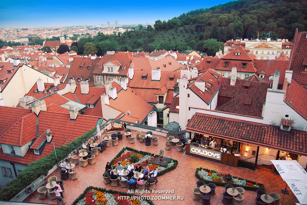 Downview to Prague red roofs and restaurant with people