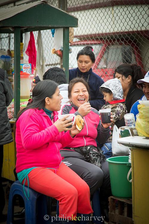 Women outside fish market. Drinking Peruvian drink Chicha, Lima, Peru, South America