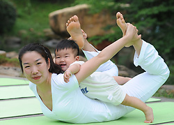 June 20, 2017 - A yoga fan practises yoga with her son during an event marking the International Yoga Day, which falls on June 21 every year, in Chenzhou, central China's Hunan Province. (Credit Image: © Huang Chuntao/Xinhua via ZUMA Wire)