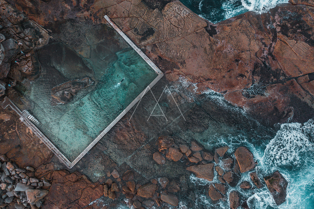 Aerial View Of Ocean Waves Breaking Over Rocks Alongside Coastal Swimming Pool With Person Swimming In Narrabeen, Sydney, Australia