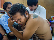 "07 MARCH 2015 - NAKHON CHAI SI, NAKHON PATHOM, THAILAND: A man grimaces as he gets a tattoo at the Wat Bang Phra tattoo festival. Wat Bang Phra is the best known ""Sak Yant"" tattoo temple in Thailand. It's located in Nakhon Pathom province, about 40 miles from Bangkok. The tattoos are given with hollow stainless steel needles and are thought to possess magical powers of protection. The tattoos, which are given by Buddhist monks, are popular with soldiers, policeman and gangsters, people who generally live in harm's way. The tattoo must be activated to remain powerful and the annual Wai Khru Ceremony (tattoo festival) at the temple draws thousands of devotees who come to the temple to activate or renew the tattoos. People go into trance like states and then assume the personality of their tattoo, so people with tiger tattoos assume the personality of a tiger, people with monkey tattoos take on the personality of a monkey and so on. In recent years the tattoo festival has become popular with tourists who make the trip to Nakorn Pathom province to see a side of ""exotic"" Thailand.   PHOTO BY JACK KURTZ"