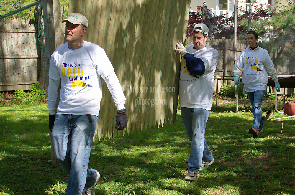 Jeff O'Connor and Roy Reale carrying new fence, and Michele Blaszko gardener in background - There's No Place Like Home, New Haven CT.