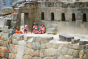 A traditionally dressed Andean family relaxes among the ruins of the Inca fortress at Ollantaytambo, Sacred Valley, Peru on September 23, 2005.