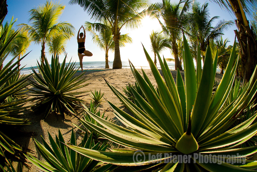 A young woman practices yoga on a beach in Mal Pais, Costa Rica.