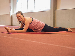 Young woman practicing yoga in athletics hall on tartan track, Offenburg, Baden-Wuerttemberg, Germany