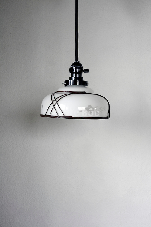 hanging from ceiling glass lamp shade with light off against a white wall