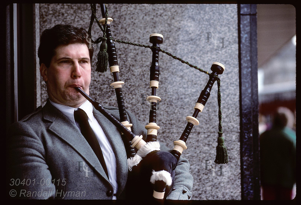 Bagpiper plays for small change from passers-by outside office building in downtown Edinburgh. Scotland