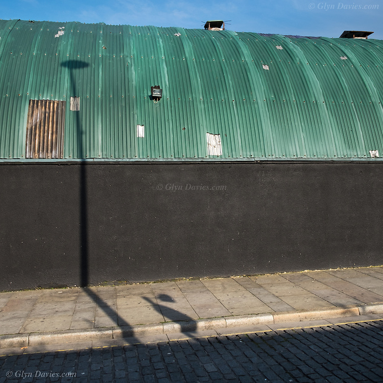 Shadows from street lights fall across a green corrugated roof of the Cream Nation Nightclub, Wolstenholme Square, Liverpool city centre.