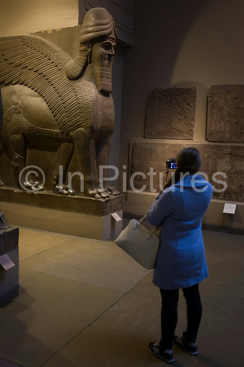 Muslim visitor takes a photo with a smartphone of a pair of giant Assyrian protective spirits - an Ugallu - or great Lion, preceded by what may be a House God from about 700-692BC from the ancient city of Nineveh, an ancient Mesopotamian city located in modern day Iraq; it is on the eastern bank of the Tigris River, and was the capital of the Neo-Assyrian Empire. It was the largest city in the world for some fifty years[1] until, after a bitter period of civil war in Assyria itself, it was sacked by an unusual coalition of former subject peoples, the Babylonians, Medes, Persians, Chaldeans, Scythians and Cimmerians in 612 BC.
