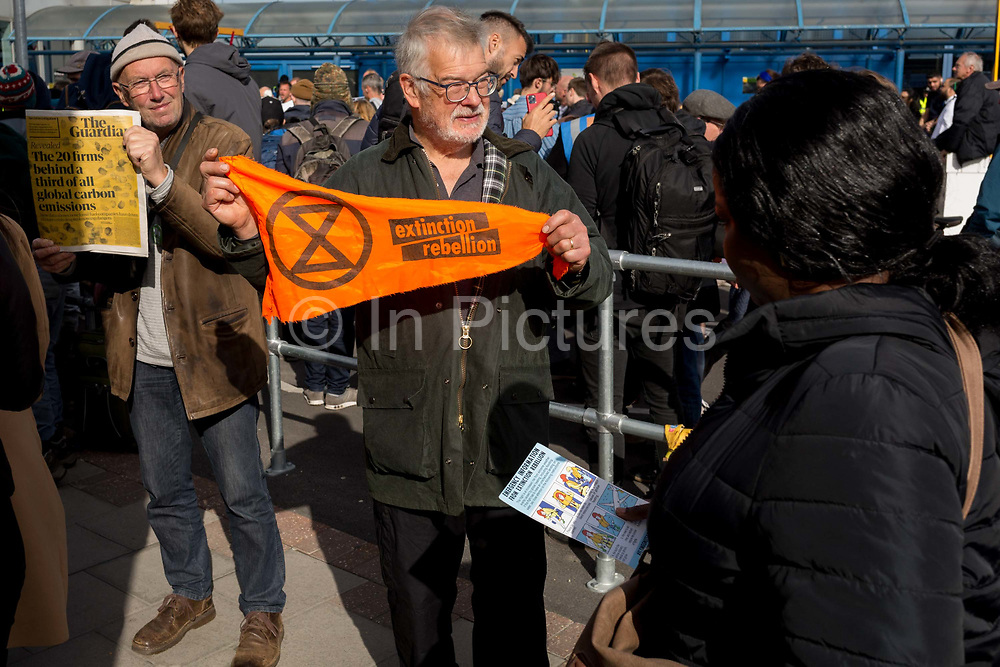 Environmental activists hand out leaflets to air passengers while protesting about Climate Change during the occupation of City Airport Londons Business Travel hub in east London, the fourth day of a two-week prolonged worldwide protest by members of Extinction Rebellion, on 10th October 2019, in London, England.
